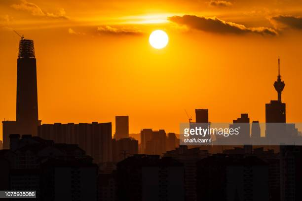 Majestic sunset over downtown Kuala Lumpur in silhouette.