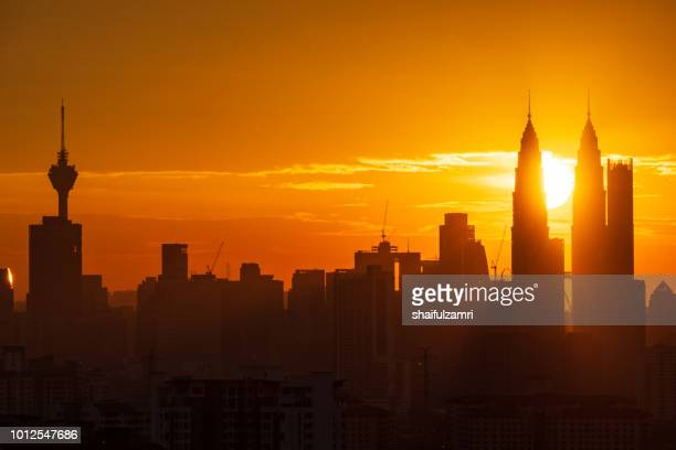 majestic sunset over twins tower and surrounded buildings in downtown kuala lumpur, malaysia. - shaifulzamri stock-fotos und bilder