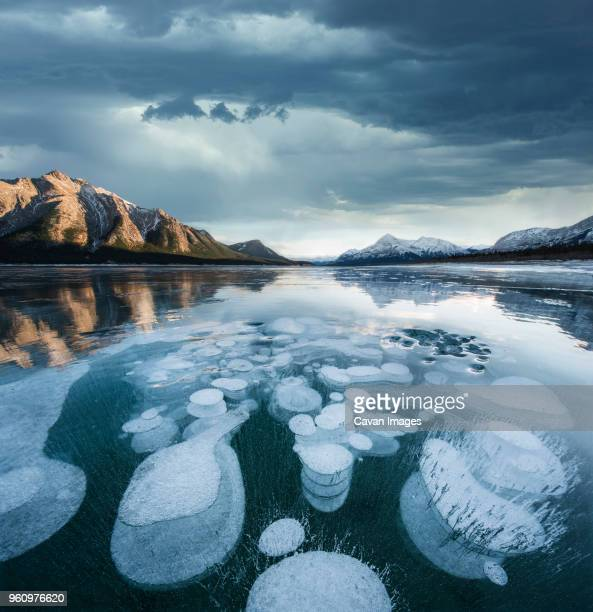 majestic view of methane bubbles in abraham lake by mountains against stormy cloudy - see abraham lake stock-fotos und bilder