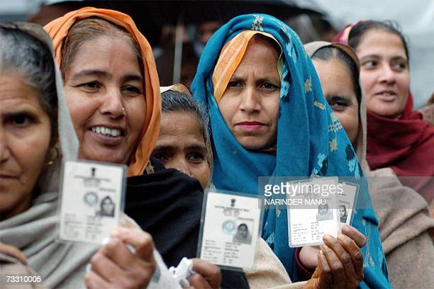 Indian village women hold up their voting cards as they await their turn to vote at a polling station in Majitha some 27 Kms from Amritsar 13...