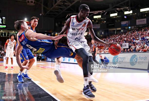 Majok Deng of the 36ers drives to the basket as Shaun Bruce of the Bullets defends during the round eight NBL match between the Adelaide 36ers and...
