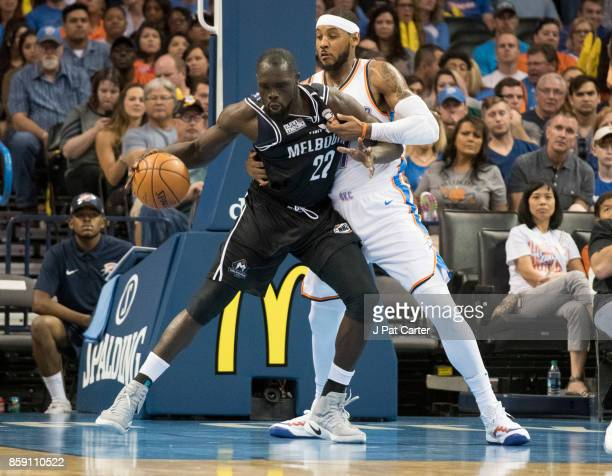 Majok Majok of Melbourne United and Carmelo Anthony of the Oklahoma City Thunder battle for the ball in the first half of a NBA preseason game at the...