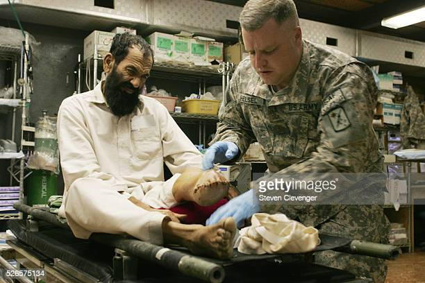 Major Brian Helsel checks the condition of a Afghan national's stump two weeks after the man's foot had been amputated. The man claimed that Taliban...