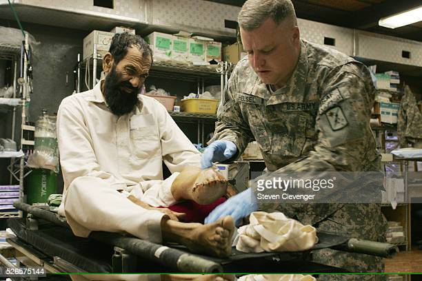 Major Brian Helsel checks the condition of a Afghan national's stump two weeks after the man's foot had been amputated The man claimed that Taliban...
