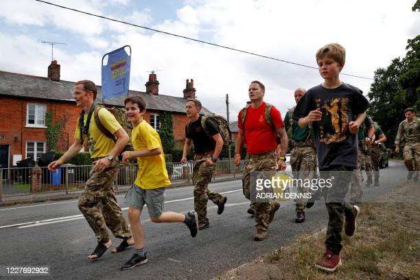 Major Chris Brannigan marches barefoot with his son Navid through Hartley Wintney a village in Hampshire on July 19 part way through his journey from...