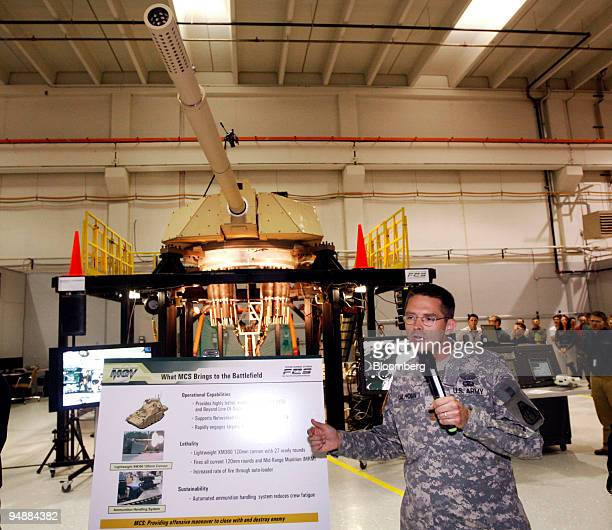 Major Cliff Calhoun of the U.S. Army speaks about a new Future Combat Systems cannon, seen at rear, at the General Dynamics Land Systems Shelby...