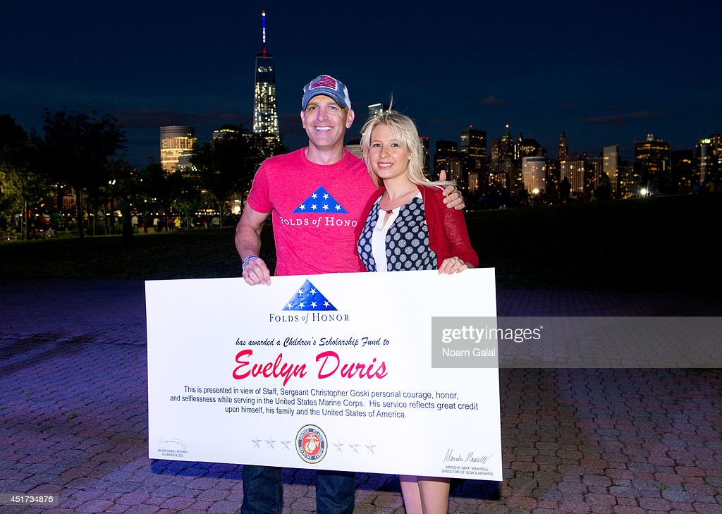 Major Dan Rooney, Folds of Honor Foundation, presents a scholarship to Mrs. Stephanie Duris at the Freedom & Fireworks Festival on July 4, 2014 in in Liberty State Park, New Jersey. The scholarship, in honor of her husband, Marine Corp Special Forces Staff Sergeant Christopher Goski, who died in the line of duty in June 2012, is one of 600 scholarships Budweiser and the Budweiser wholesaler network will provide to American military families through its $3 million donation to Folds of Honor in 2014.