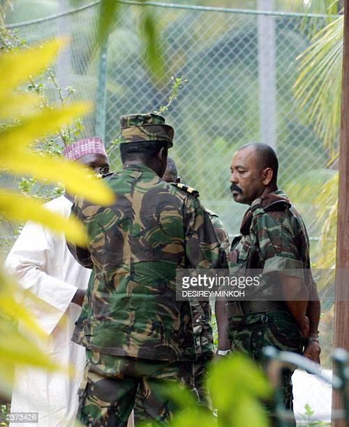 Major Fernando Pereira nicknamed Cobo talks with Arlesio Costa chief of the Buffalos and Sao Tome's Nigerian ambassador 23 July 2003 at the Marlin...