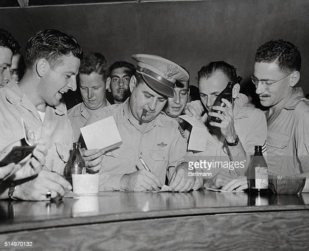Major General Curtis E LeMay is seen signing autographs for GIs on Guam