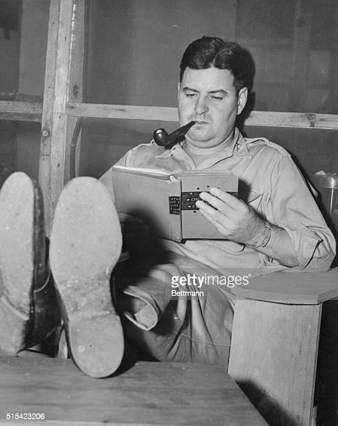 Major General Curtis E LeMay of Cleveland Ohio commanding general of the 21st Bomber Command props his feet on a wooden table as he relaxes with a...
