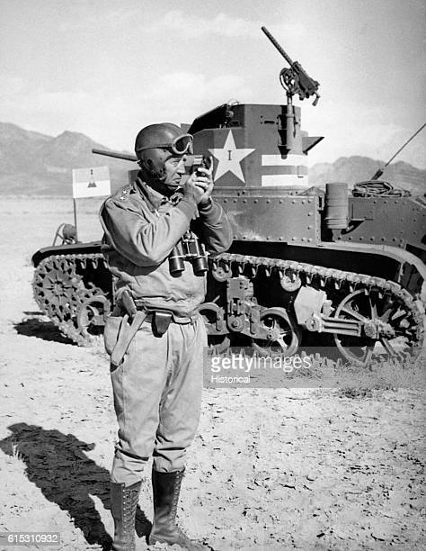 Major General George S Patton Jr takes a sighting with a compass He is standing next to a tank North Africa 1942