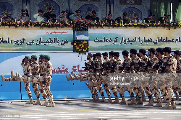 Major General Hassan Firoozabadi salutes alongside other military commanders as they observe a parade commemorating the 31st anniversary of Iran-Iraq...