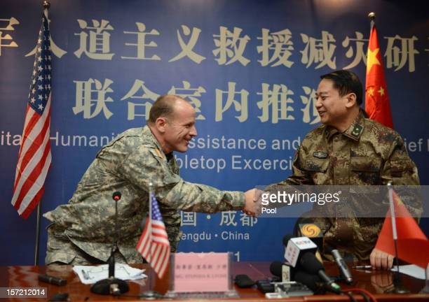 Major General Stephen R Lyons of the US Army Pacific and Major Tang Fen of China's People's Liberation Army shake hands at the end of a twoday...