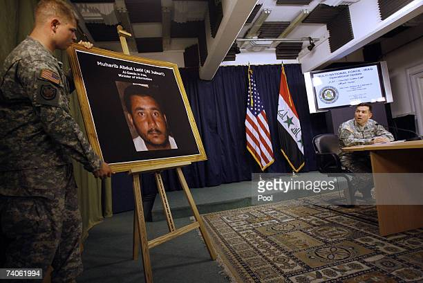 S Major General William Caldwell commander of the MultiNational Force Iraq speaks during a press conference as a soldier holds a picture of a man...