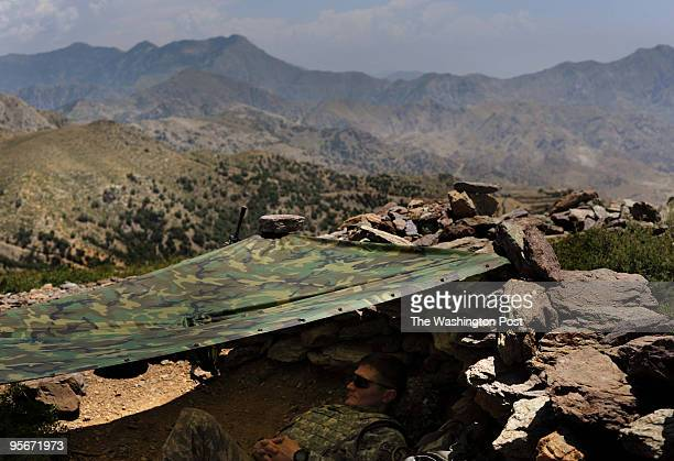Major Jason Dempsey relaxes under the makeshift shade of a poncho on a scorching day along the ridge bordering Pakistan and Afghanistan on Wednesday...