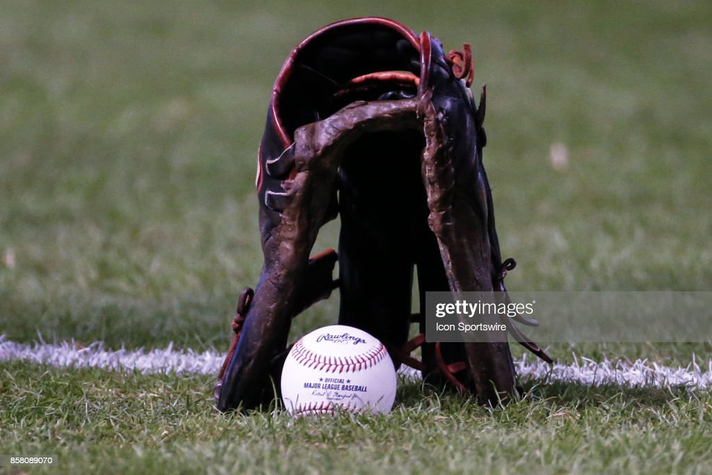 A Major League Baseball and glove on the field before the MLB National League Wild Card baseball game between the Colorado Rockies and the Arizona Diamondbacks on October 4, 2017 at Chase Field in Phoenix, Arizona.