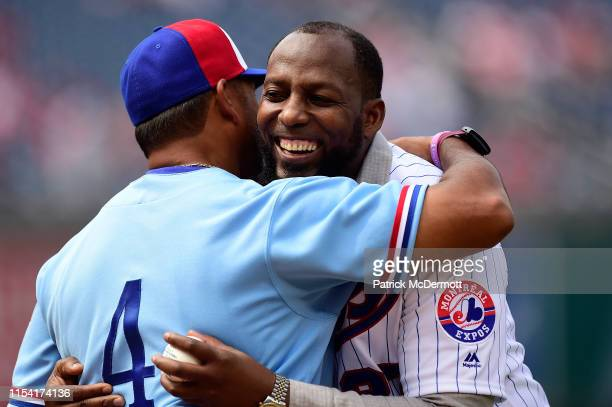 Major League Baseball Hall of Famer Vladimir Guerrero hugs Washington Nationals mananger Dave Martinez after throwing out the ceremonial first pitch...