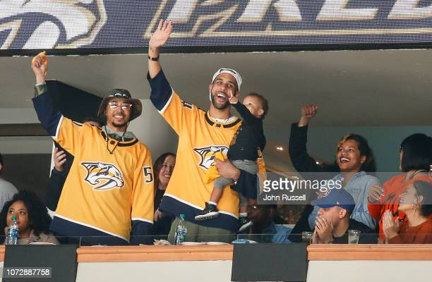 Major League Baseball players Mookie Betts and David Price wave to fans during an NHL between the Nashville Predators and the Vancouver Canucks at...