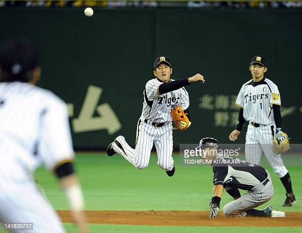 US Major League baseball team Seattle Mariners Ichiro Suzuki slides towards second base while Japan's Hanshin Tigers second baseman Keiichi Hirano...