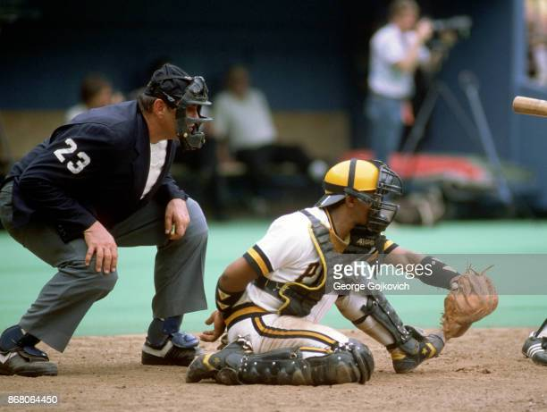 Major League Baseball umpire Lee Weyer looks over the shoulder of catcher Tony Pena of the Pittsburgh Pirates during a game at Three Rivers Stadium...