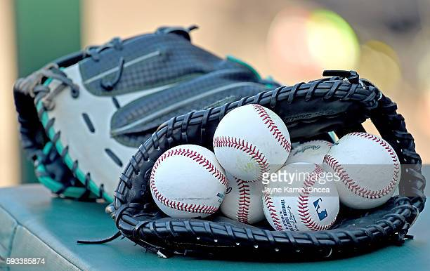 Major league baseballs sit in a glove as the Seattle Mariners warm up before the game against the Los Angeles Angels at Angel Stadium of Anaheim on...