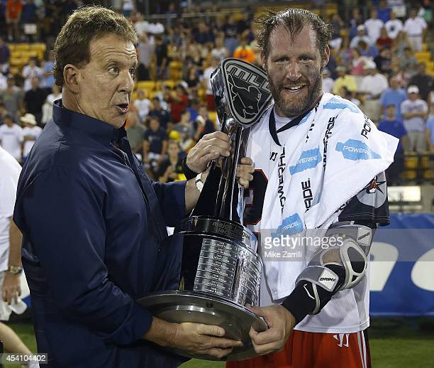 Major League Lacrosse League founder Jake Steinfeld hands the Steinfeld Trophy to attacker John Grant Jr of the Denver Outlaws after the 2014 Major...