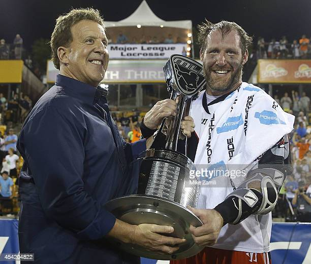 Major League Lacrosse League founder Jake Steinfeld hands the Steinfeld Trophy to attacker John Grant Jr #24 of the Denver Outlaws after the 2014...