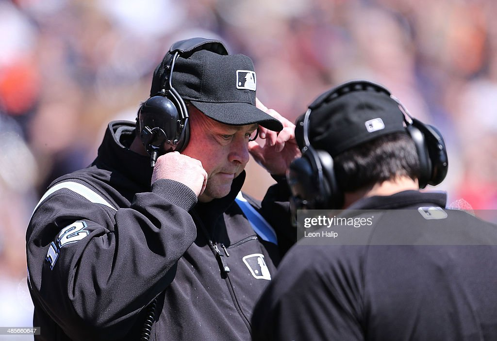 Major League Umpire Gerry Davis #12 uses the instant replay review system to check on a challanged call made during the game between the Los Angeles Angels of Anaheim and the Detroit Tigers at Comerica Park on April 19, 2014 in Detroit, Michigan. The Tigers defeated the Angels 5-2.