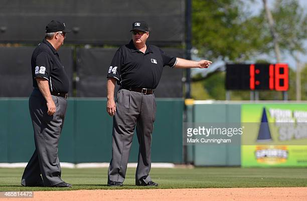 Major League umpires Joe West and Jerry Layne stand together on the field while the new baseball paceofplay inning break clock is shown in the...