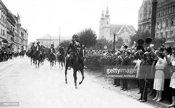 Major Ostenburg leads a detachment of gendarmes through Sopron in support of the WestHungarians who are protesting the Trianon Treaty which would...