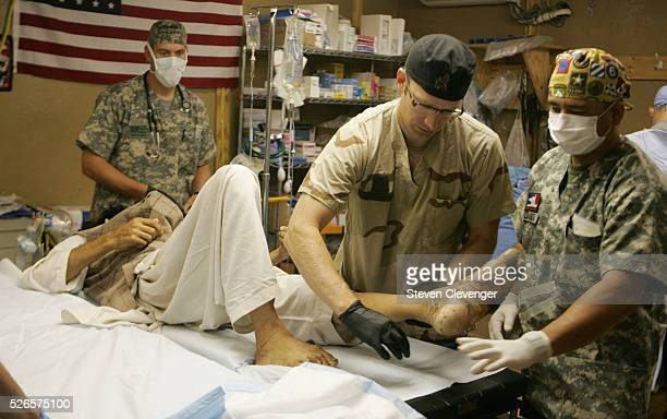 Major Randy Kjorstad with Pfc Bryant Alaniz lifts and positions the foot of a Afghan civilian in the operating room of the 758th Forward Surgical...