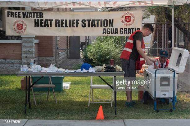 Major Tim Smith, right, and volunteer Adrian Keller fill a cooler with water at a heat relief station at the Salvation Army Phoenix Citadel on June...