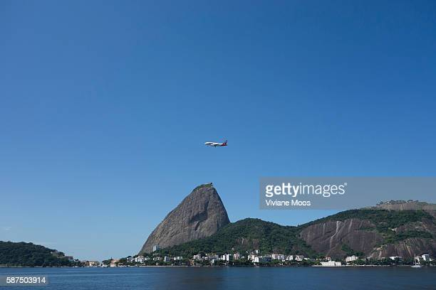 A major tourist attraction Sugar Loaf rises across the Guanabara bay while a plane flies overhead on it's way out of Rio