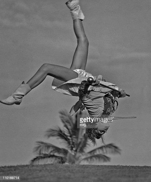 A majorette doing a somersault with a baton in her hand circa 1950