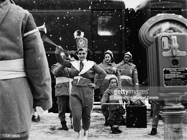 A majorette in uniform is twirling her baton to the sound of a marching band in distinctive costumes Sherbrooke Quebec Canada 1958 Photo taken during...