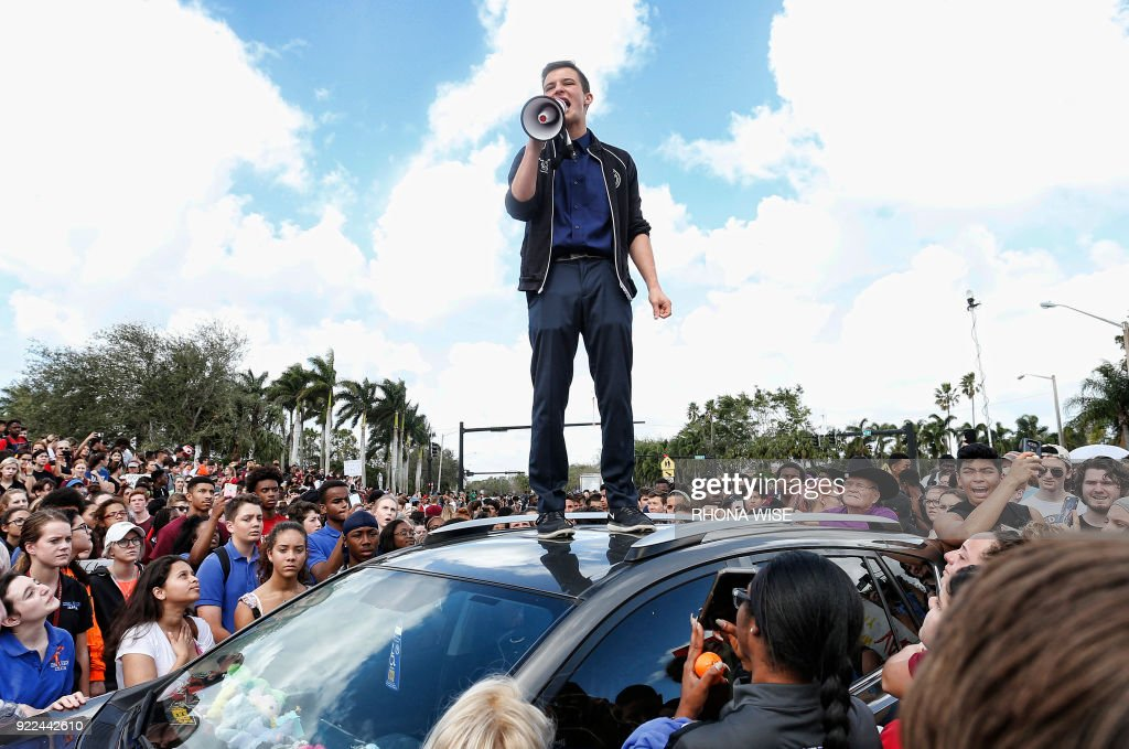 Majory Stoneman High School student Cameron Kasky addresses area High Schoolstudents as they rally at Marjory Stoneman Douglas High School after participating in a county wide school walk out in Parkland, Florida on February 21, 2018. A former student, Nikolas Cruz, opened fire at Marjory Stoneman Douglas High School leaving 17 people dead and 15 injured on February 14. /