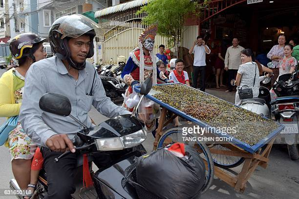 Mak Sobin pushes his cart loaded with dried river shells for sale along a street in Phnom Penh on January 14, 2017. Mak Sobin who has been selling...