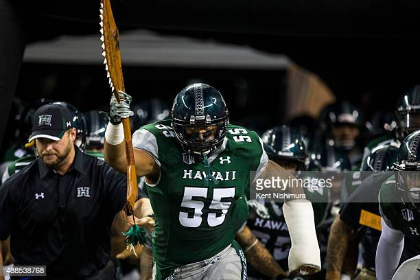 Makani KemaKaleiwahea of the Hawaii Warriors leads the Hawaii Warriors out onto the field before the start ofthe first quarter of a college football...