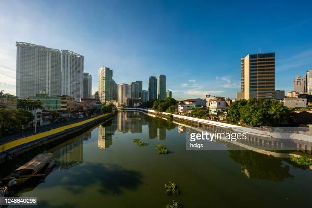 makati stadt skyline in metro manila während covid krise von brücke über pasig fluss gesehen - hauptstadtregion stock-fotos und bilder