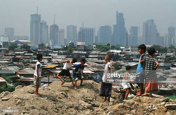 Children play outside in front of their slum housing with the Makati business district skyline in the background In the Philippines there is a huge...