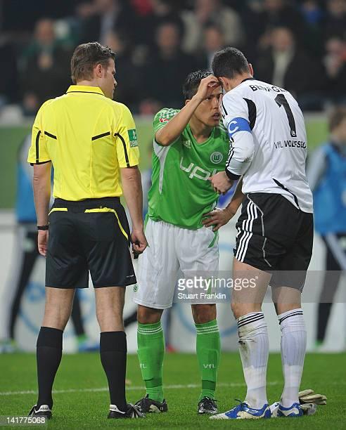 Makato Hasebe checks the eye of Diego Benaglio of Wolfsburg as referee Doctor Feix Bryce watches during the Bundesliga match between VfL Wolfsburg...