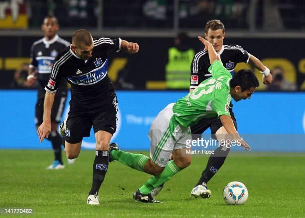 Makato Hasebe of Wolfsburg and Mladen Petric of Hamburg battle for the ball during the Bundesliga match between VfL Wolfsburg and Hamburger SV at the...