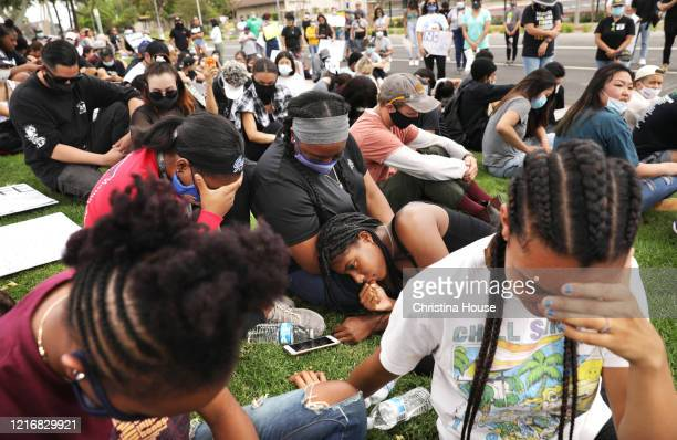 Makayla Wade Sydni Jones Jordan Wade Monae McCalebb and Ava Quillard from left bow their heads to join in prayer with demonstators during a peaceful...