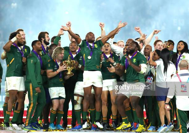 Makazole Mapimpi of South Africa and teammates celebrate as Faf de Klerk holds the Web Ellis cup following their team's victory against England in...
