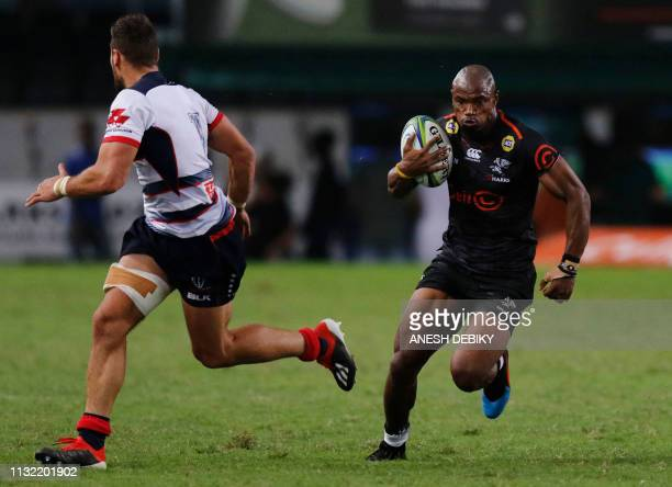 Makazole Mapimpi of the Cell C Sharks runs with the ball next to Tom English of the Melbourne Rebels during the Super Rugby match at the Kings Park...