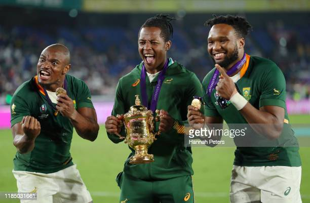 Makazole Mapimpi S'Busiso Nkosi and Lukhanyo Am of South Africa celebrate with the Web Ellis Cup following their team's victory over England in the...