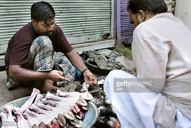 Makdhom an Indian street butcher prepares buffalo feet for a customer in a street behind the Jama Masjid in Old Delhi 23 August 2003 India's...