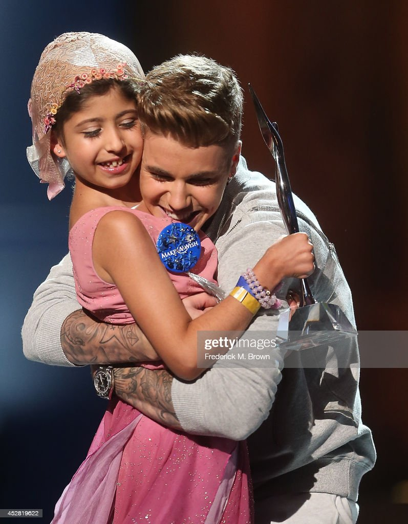 Make a Wish recipient Wish Child Grace and Singer Justin Bieber (R) onstage at the 2014 Young Hollywood Awards brought to you by Samsung Galaxy at The Wiltern on July 27, 2014 in Los Angeles, California. The Young Hollywood Awards will air on Monday, July 28 8/7c on The CW.
