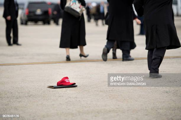 A Make America Great Again hat is seen on the ground as people take group photos while US President Donald Trump boards Air Force One at Andrews Air...