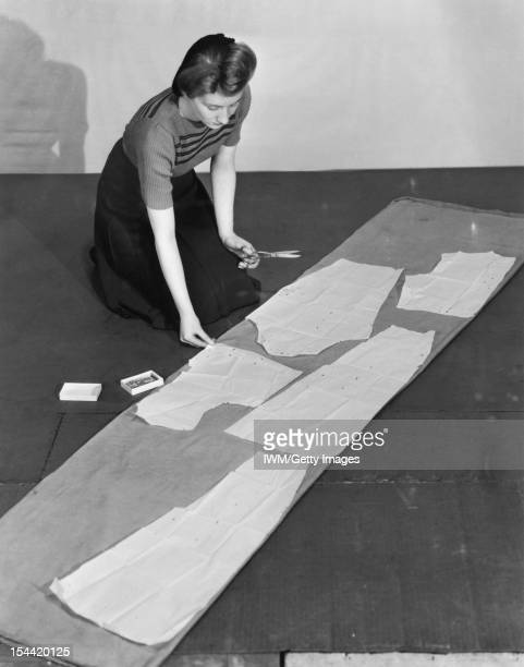 Wartime Clothing In Britain A woman cuts out sections of material from a large piece of curtain or other such fabric, using a paper pattern as a...